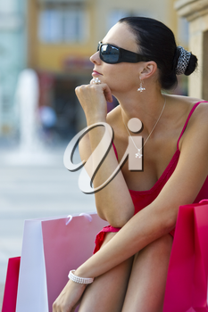 A classically beautiful Mediterranean woman sitting and thinking surrounded by full shopping bags