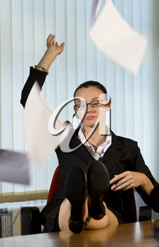 An attractive young female businesswoman throws a handfull of papers into the air in frustrated resignation