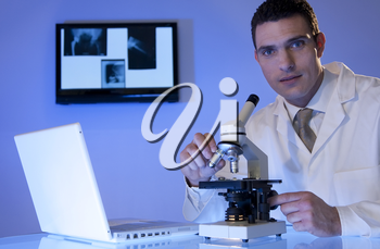 A male medical or scientific researcher using his microscope and laptop, behind hima are some x-rays on a light box