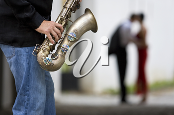A street musician plays his saxophone while a romantic couple can be seen out of focus in the background