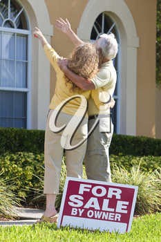 A senior retired man and woman looking at a house for sale with the sign in the foreground