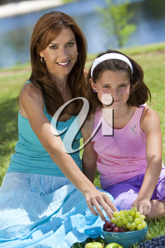 Woman and girl, mother and daughter, together outside in the countryside eating healthy fruit at a picnic by a lake