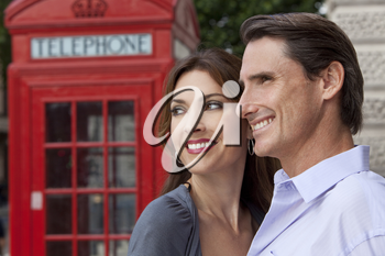 A romantic happyman and woman couple in London, England, with a classic red telephone box out of focus behind him