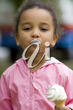A beautiful mixed race little girl eating an ice cream and blowing a kiss to the camera