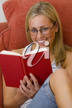 A beautiful blue eyed, blond haired, woman relaxing and reading a hardback book