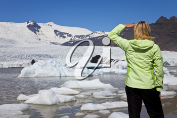 Environmental picture of woman hiker dressed in green jacket looking at the effects of global warming climate change on a melting glacier with icebergs floatiing into a glacial pool.