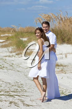 Man and woman romantic happy couple in white clothes walking on a deserted tropical beach with bright clear blue sky