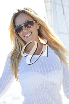 A beautiful young woman in sunglasses standing on the deck of a sail boat on a calm blue sea