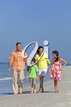 A happy family of mother, father and two children, son and daughter, walking and having fun in the sand of a sunny beach