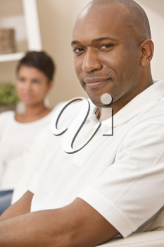 A happy African American man and woman couple in their thirties sitting at home, the man is in focus in the foreground the woman out of focus in the background.