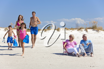 A happy family of mother, father, two children, son and daughter, running having fun on a sunny beach while the grandparents sit looking on and laughing.