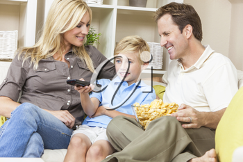 An attractive happy, young family of mother, father and son sitting on a sofa at home watching television the boy is using the remote control
