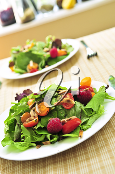 Healthy green salad with berries and cherry tomatoes