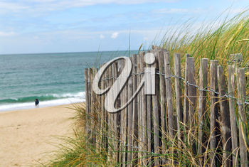 Ocean with sandy beach and wooden fence