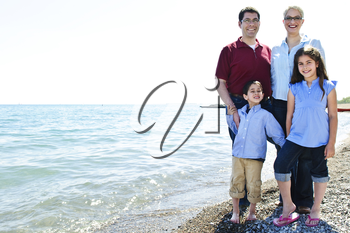 Happy family standing on shore at the beach