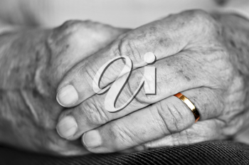 Close up on elderly woman hands with golden wedding ring
