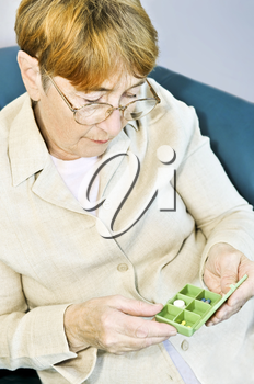 Elderly woman holding pill box with medication