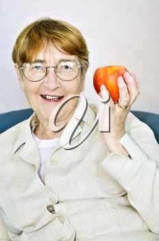 Elderly woman eating healthy holding a nutritious apple