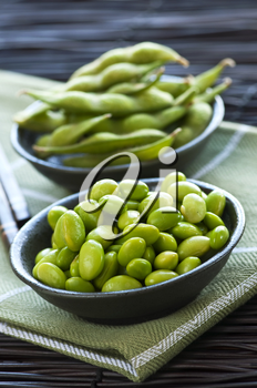 Edamame soy beans shelled and with pods in bowls