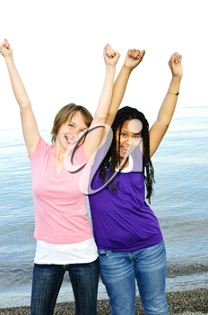 Portrait of two teenage girl friends raising arms