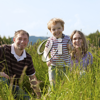 Very happy family with son sitting in a� meadow in the summer sun in front of a forest and hills, they are nearly hidden by the high grass, very peaceful scene