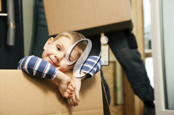 Family moving in their new home. The son is sitting inside a moving box. In the background the father - or a mover (only legs to be seen) is carrying boxes inside the building