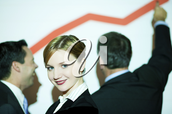 Business team standing in front of business graph projected on wall (people illuminated by projector, there are wirelines from projection on people and screen, selective focus on girl in front)