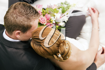 wedding couple hugging and kissing, the bride holding a bouquet of flowers in her hand