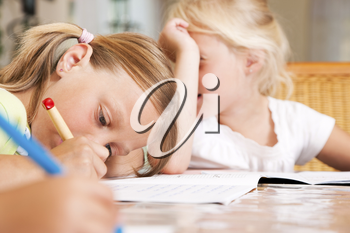 Children doing homework for school together helping each other