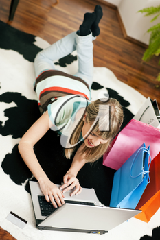 Woman lying in her home living room on floor shopping or doing banking transactions online in the Internet, emphasized by shopping bags in the background�