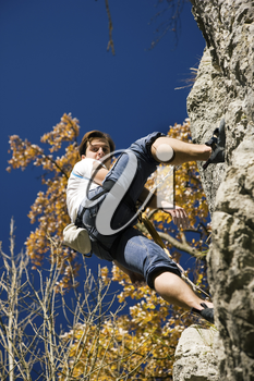 Man climbing a rock at a perfect clear autumn day in the mountains