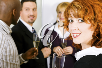 Group of people having a toast or party with champagne standing together, one woman in front looking at the viewer