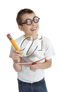 Geeky student child wearing glasses.  He is smiling and holding a notebook and oversized pencil.    PLEASE NOTE: eyeglasses are fake and are intended to make eyes look distorted.