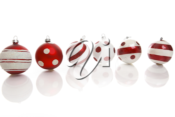 Red and white Christmas baubles on a white background with space for copy.