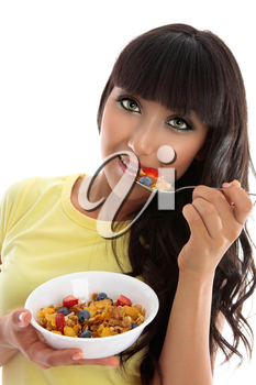 A female eating a healthy nutritional breakfast of cereals grains and fruit