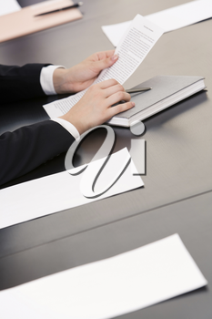 Image of human hands holding pen and documents with notebook, papers near by on the table