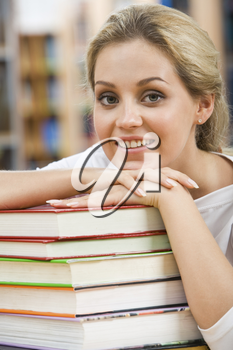 Portrait of pretty student putting her chin on hand over pile of books