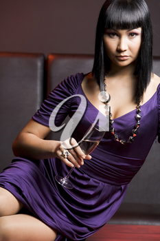 Portrait of charming female sitting on table with flute of champagne in hand