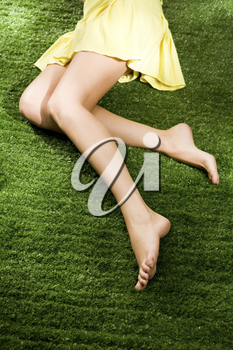 Close-up of slim female legs on soft green grass during relaxation