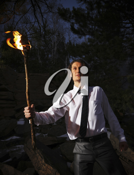 Image of brave man with burning stick in darkness