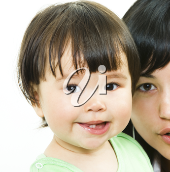 Close-up of small girl�s face looking at camera with her mother on the background