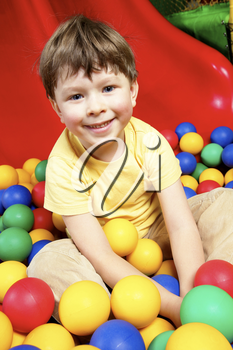 Happy lad looking at camera while sitting in balls