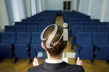 Rear view of lecturer�s head in front of rows of armchairs in conference hall