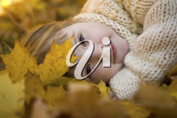 Head of girlie lying on golden leaves in autumn with peaceful expression