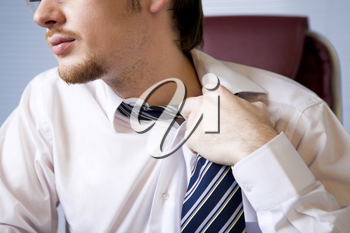 Close-up of annoyed businessman loosing his tie to relax a bit after hard work
