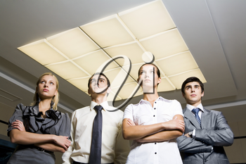 Portrait of smart associates standing in row and looking upwards seriously