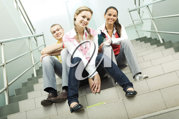 Portrait of three teens sitting on stairs and looking at camera in the  college