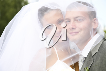 Portrait of happy bride and groom touching each other by cheeks and looking at camera