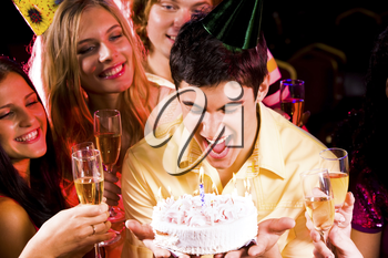 Portrait of smart guy blowing onto candles on birthday cake surrounded by friends with flutes