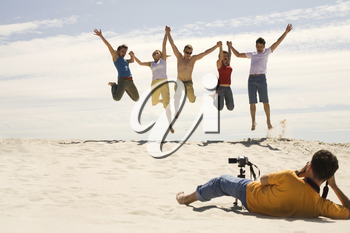 Professional photograpther taking shots of joyful friends jumping on sandy beach against blue sky